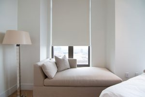 Window seating with a view through modern window treatments.